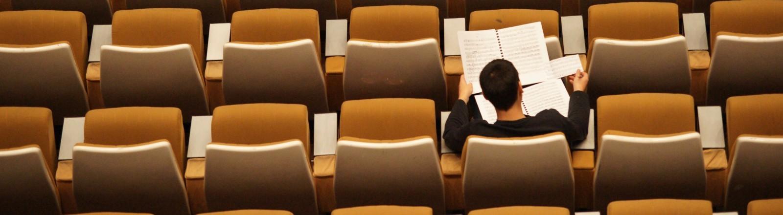Ein Mann sitzt in einem bestuhlten Konzertsaal.