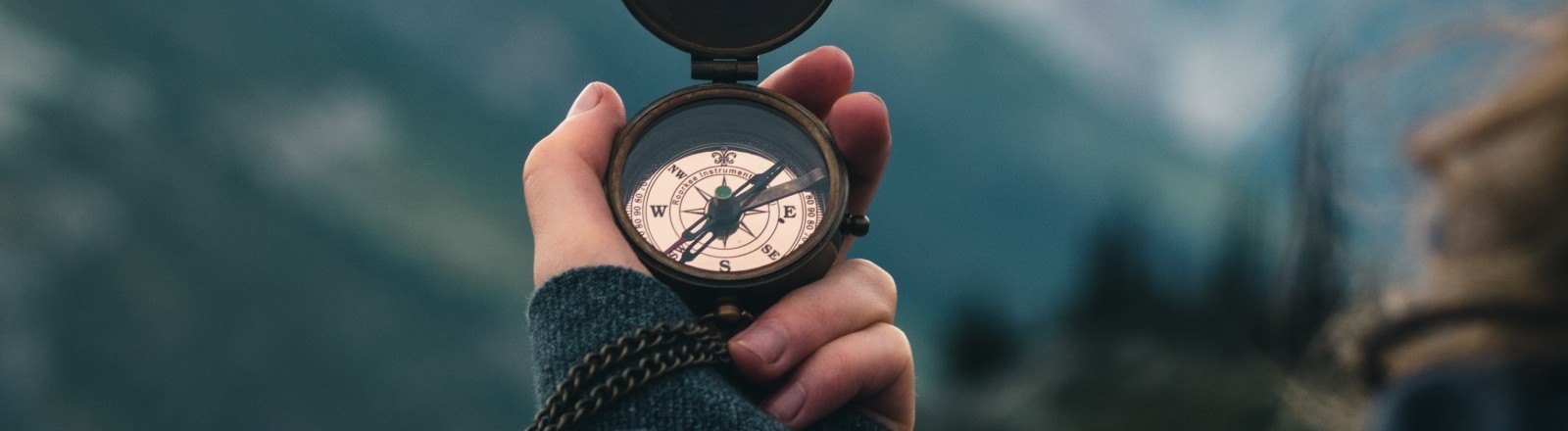 Eine Frau hält einen Kompass in der Hand.