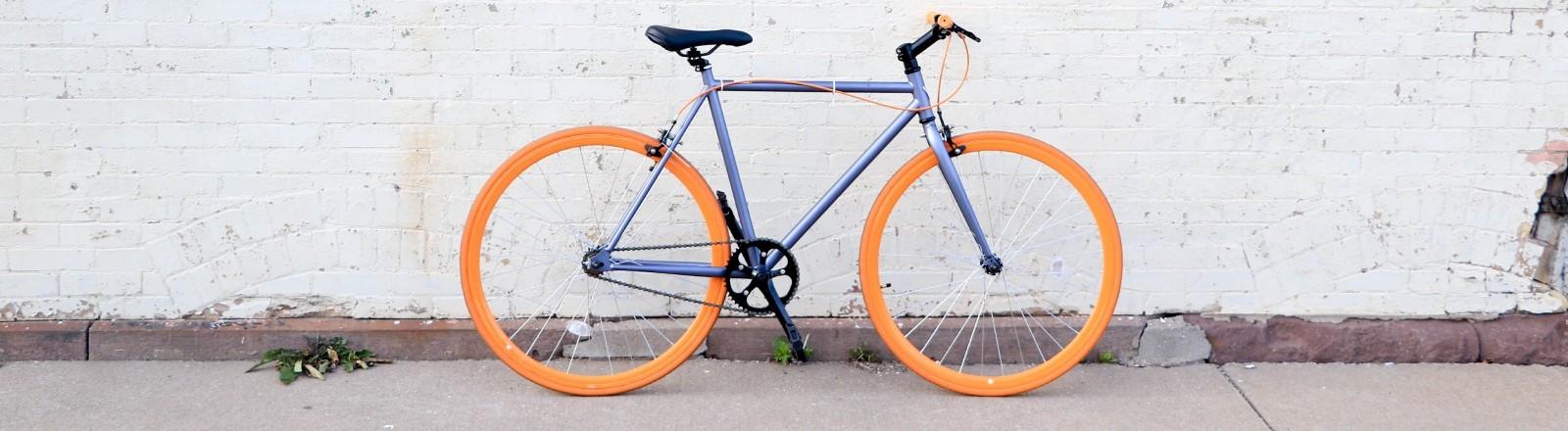 Ein Rennrad steht vor einer Wand.