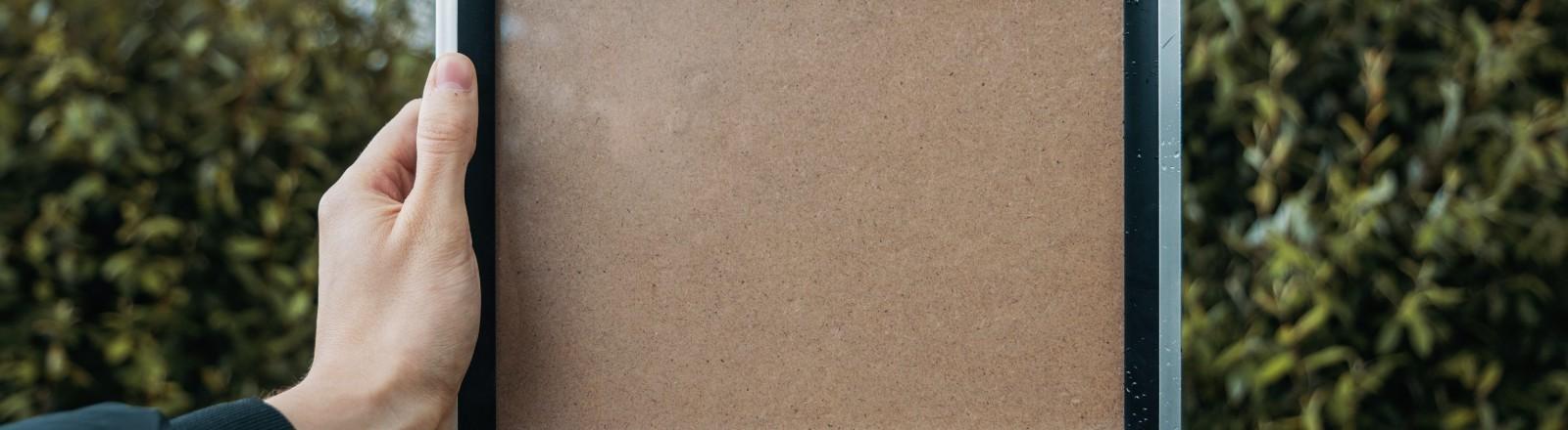 Eine Person hält einen leeren Bilderrahmen hoch.