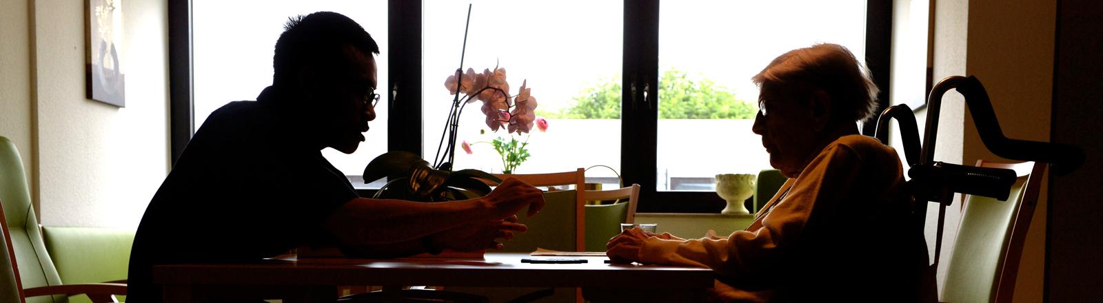 Ein Asiate sitzt mit einer älteren Dame am Tisch.