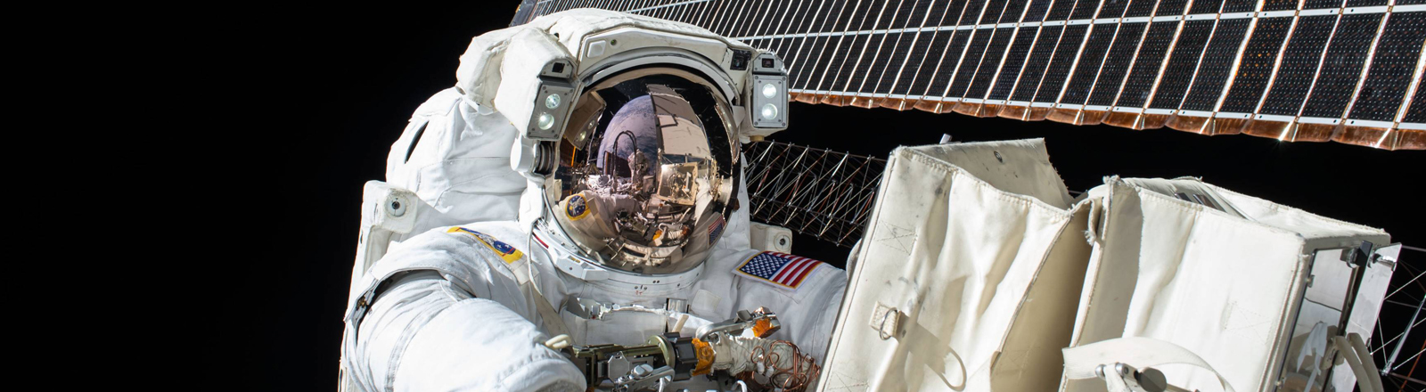 Ein Astronaut in Schutzanzug, der gerade von außen an der Internationalen Raumstation arbeitet.