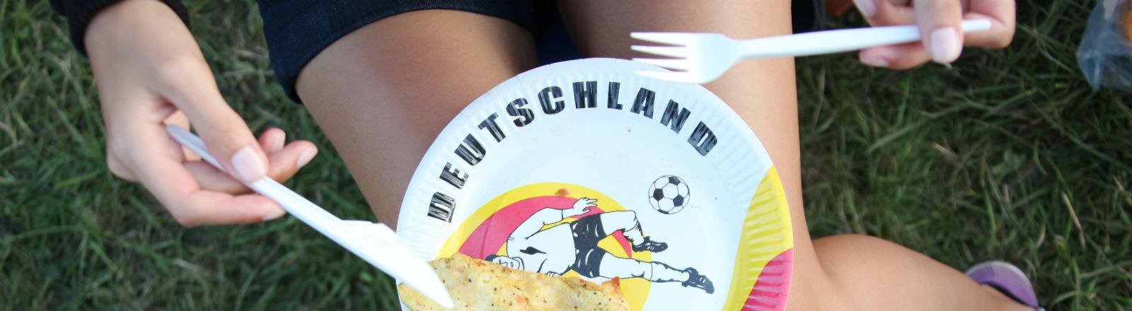 """Eine Frau mit einem Pappteller auf dem Schoß, auf dem ein Stück Fleisch liegt und """"Deutschland"""" steht."""