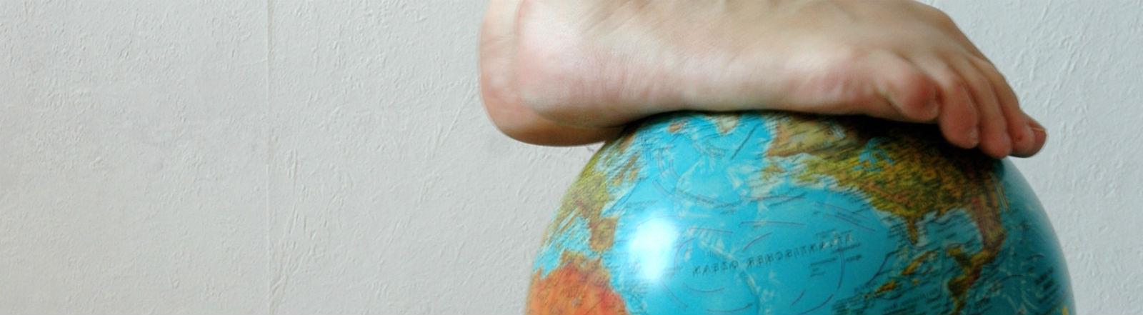 Zwei nackte Füße stehen vor einer tapezierten Wand auf einem Globus.