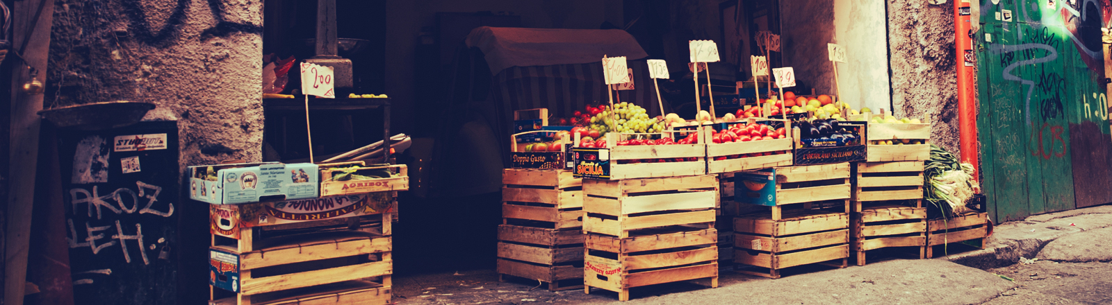 Ein Marktstand mit Holzkisten vor einem offenen Tor.