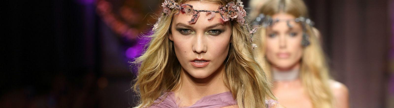 Ein Model mit einem Haarband und einem lilafarbenen Kleid.