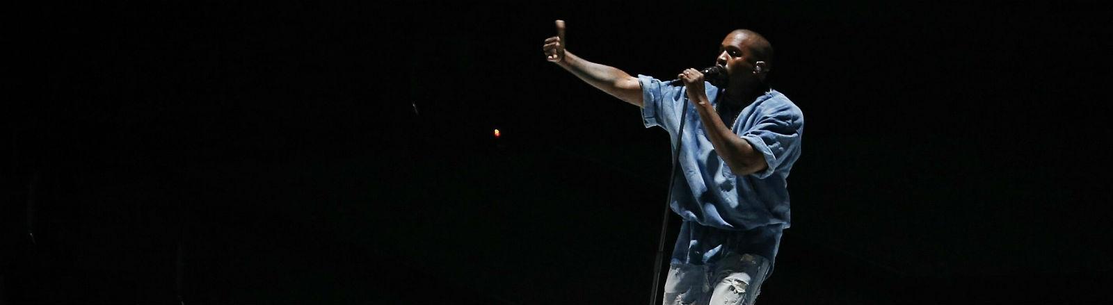 Der Rapper Kanye West auf der Bühne, in Jeanskleidung, vor schwarzem Hintergrund.