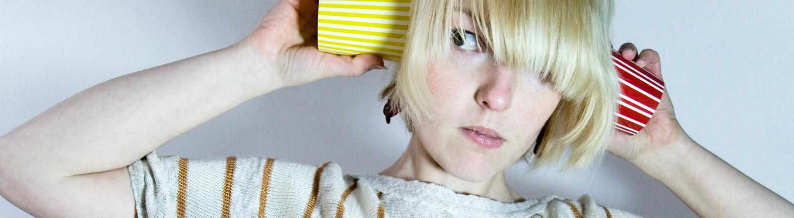 Eine junge Frau hält sich je einen Pappbecher ans Ohr und guckt verwirrt.