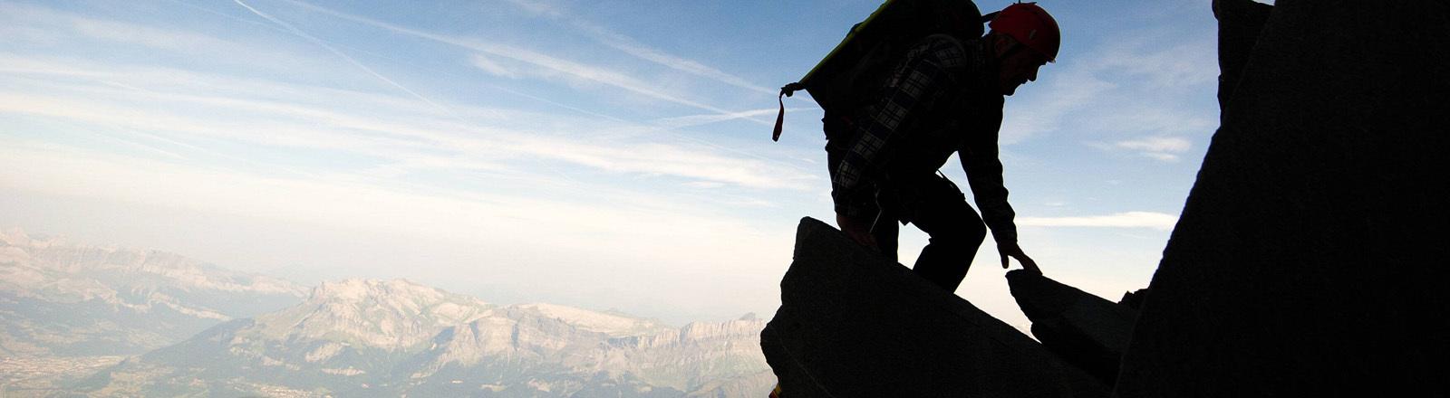 Ein Bergsteiger klettert auf einem Vorsprung, im Hintergrund ist ein Tal zu sehen.