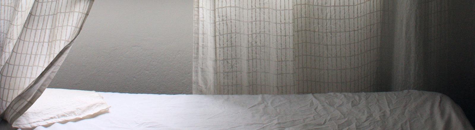 Das Bett bei offenem Fenster
