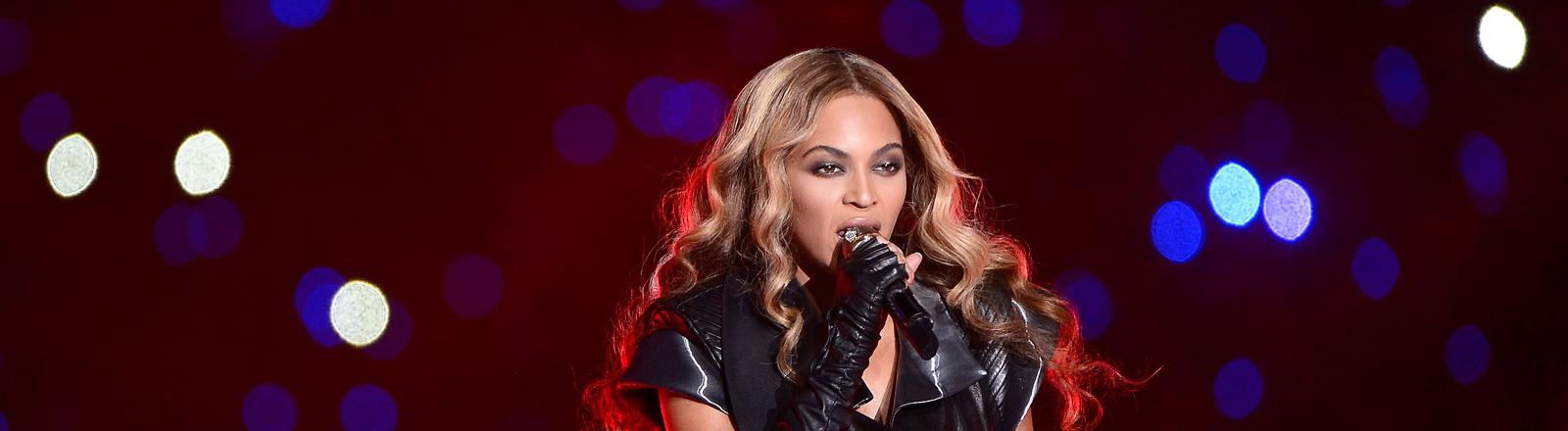 Beyoncé auf der Bühne mit Mikrofon in der Hand. Bild: dpa.