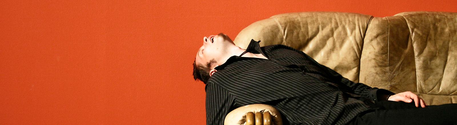 Ein Mann liegt auf einer Couch