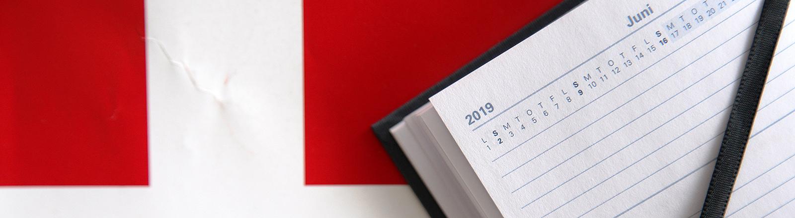 """LLUSTRATION - 06.03.2019, Dänemark, Kopenhagen: Ein aufgeschlagener Kalender liegt in Kopenhagen auf einer Dänemark-Flagge aus Papier. Der 17. Juni ist der Tag, an dem die diesjährige Parlamentswahl in Dänemark allerspätestens stattfinden muss. Wann die Wahl genau abgehalten wird, ist 100 Tage vor dem letzten möglichen Datum noch völlig unklar. (zu dpa """"Die dänische Ungewissheit - Løkkes Poker um das Wahldatum"""" am 08.03.) Foto: Steffen Trumpf/dpa"""