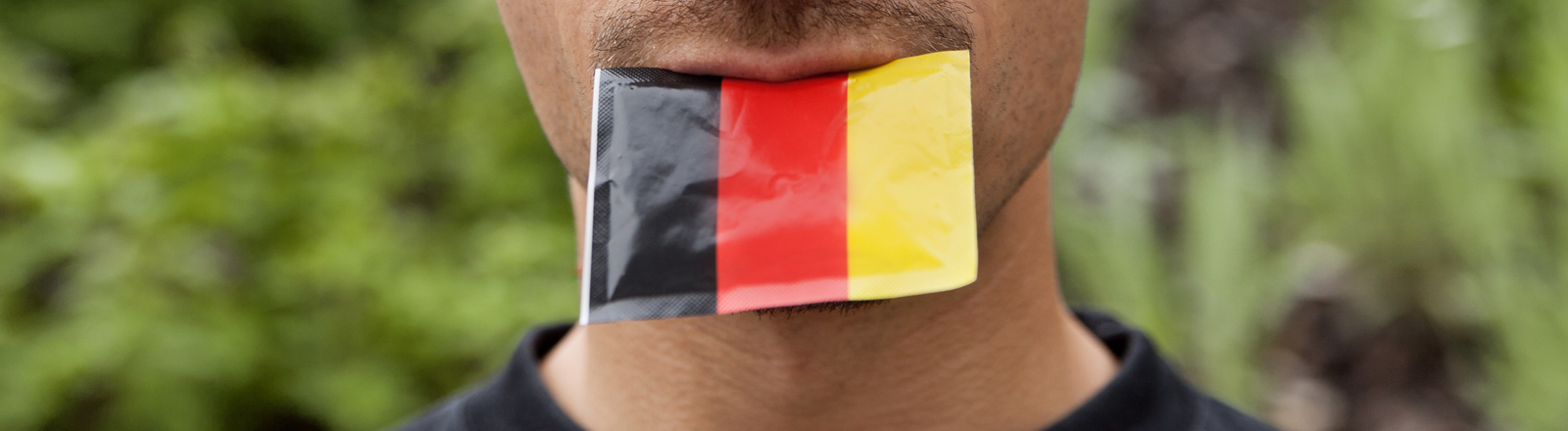 Ein Mann mit einer deutschen Fahne im Mund
