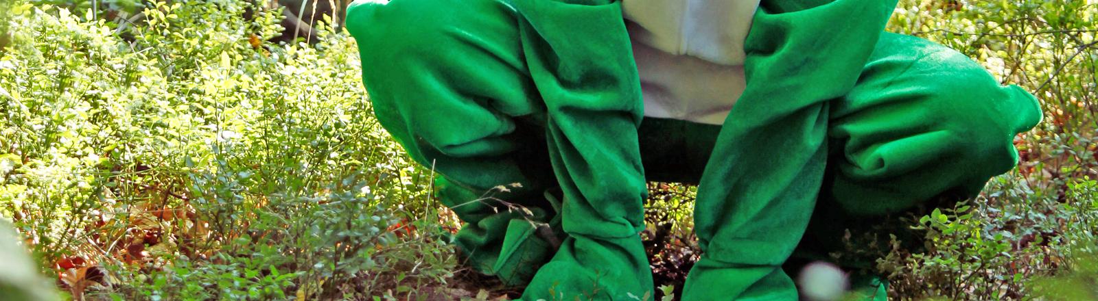 Mensch in einem Froschkostüm in der Hocke
