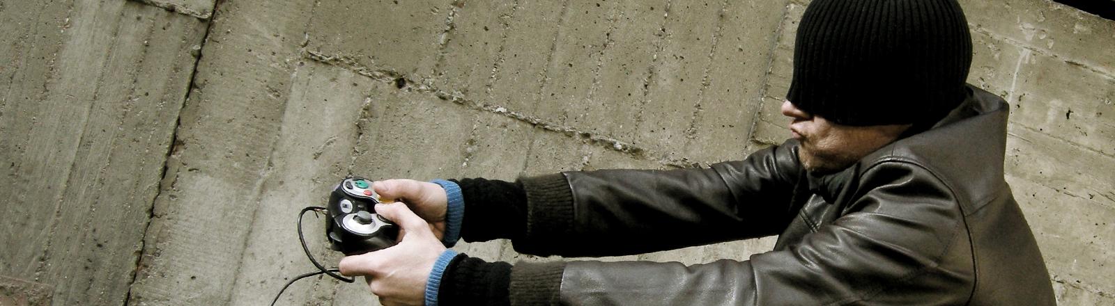 Mann mit Mütze und Gamepad in der Hand