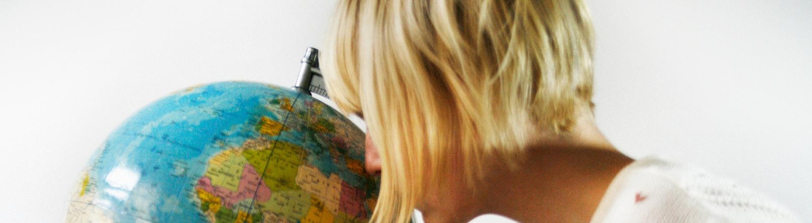 Ein Frau schaut auf einen Globus