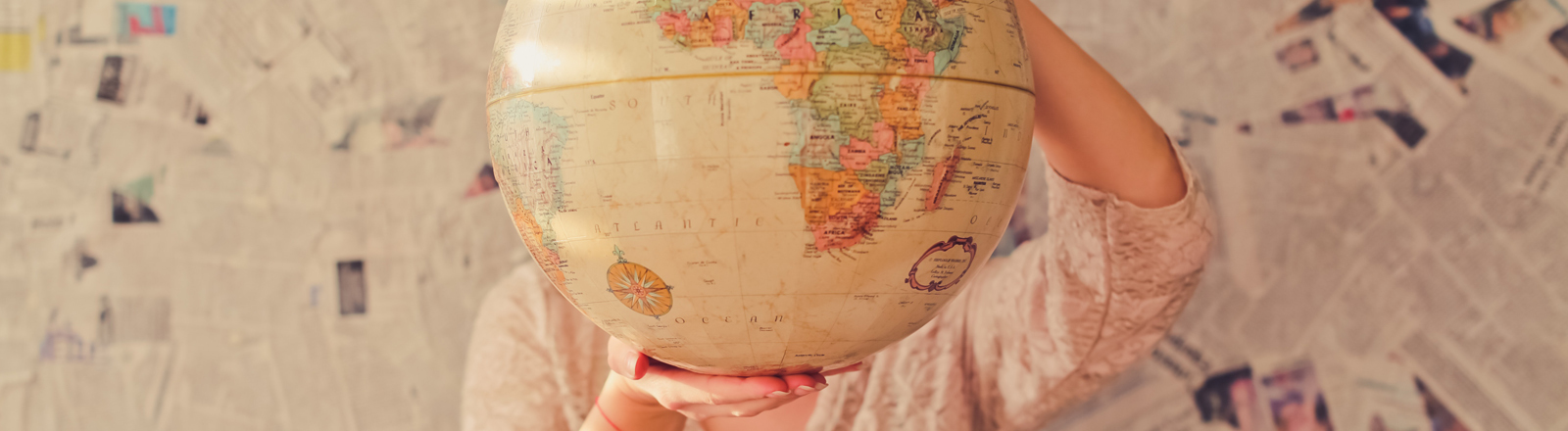 Frau mit Globus vor Gesicht