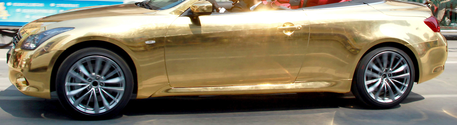 A sports car covered by gold foils drives on Huaihai Road in Nanjing, capital of east Chinas Jiangsu Province, March 29, 2011. The car, part of a promotional event of a local company, was trailered by the police as it attracted a crowd of onlookers which caused a traffic congestion and it has no license plate. Foto: Song Qiao