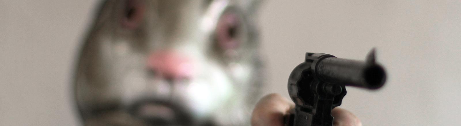 Ein Mensch mit Hasenmaske und Pistole