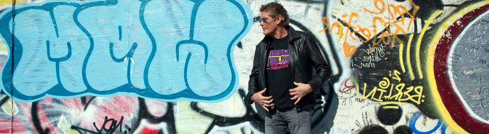 David Hasselhoff vor einem Stück Berliner Mauer