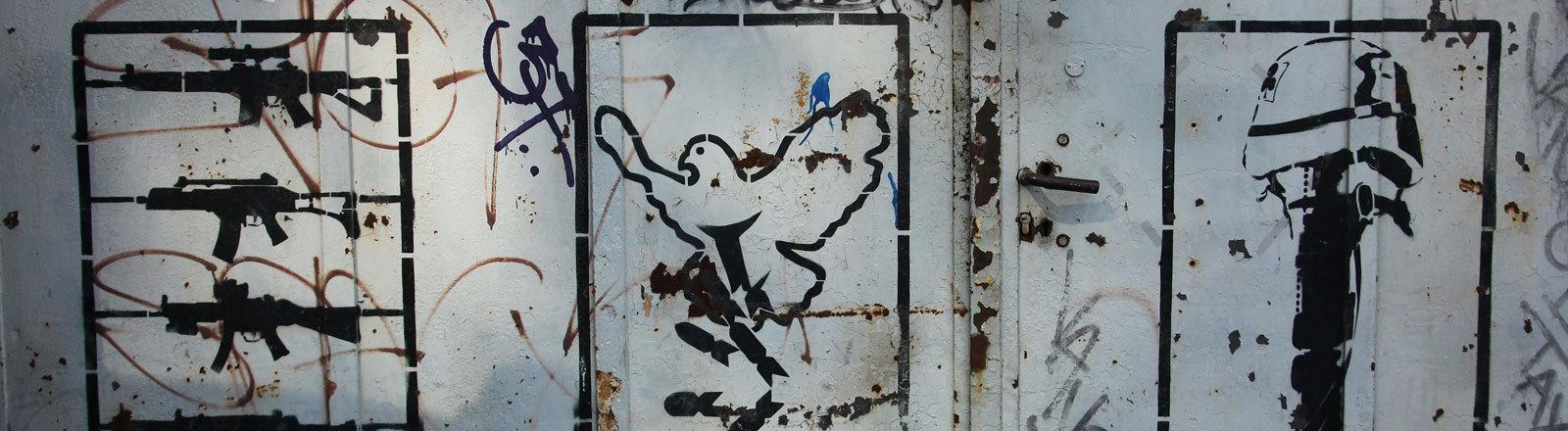 Motive des Berliner Street-Art-Künstlers Emess zum Thema Krieg und Frieden auf einer alten Eisentür auf einer Industriebrache, aufgenommen in Berlin im Bezirk Kreuzberg am 03.04.2014. Berlin ist ein Zentrum für Street Art, das Künstler aus dem In- und Ausland anzieht.