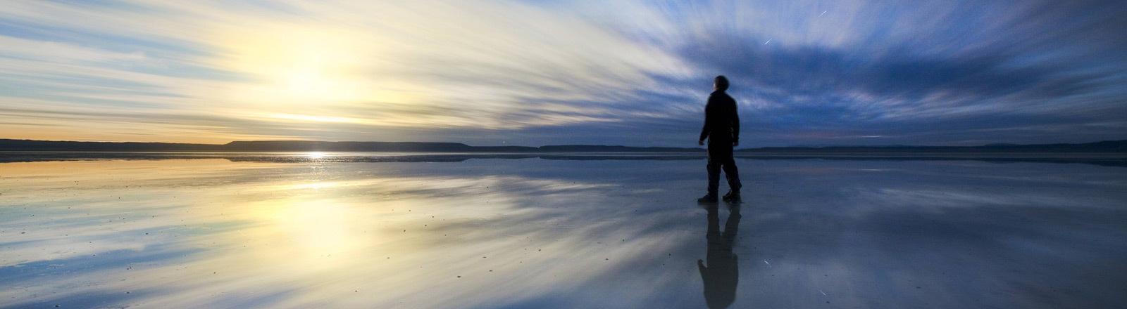 Ein Mann schaut im Sonnenuntergang aufs Meer