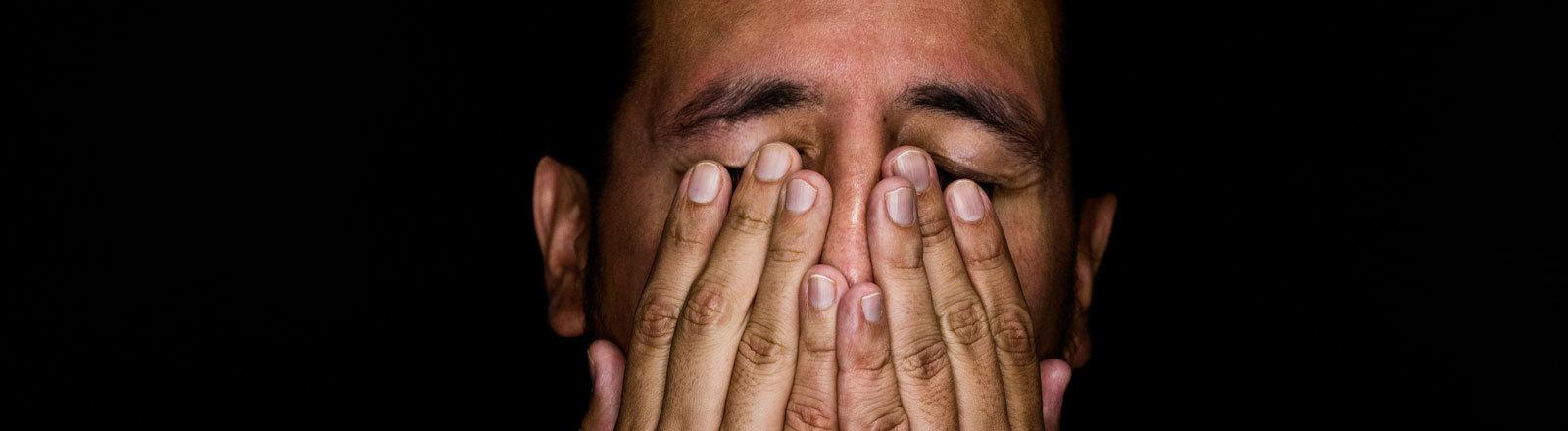 Mann schlägt Hände vors Gesicht.