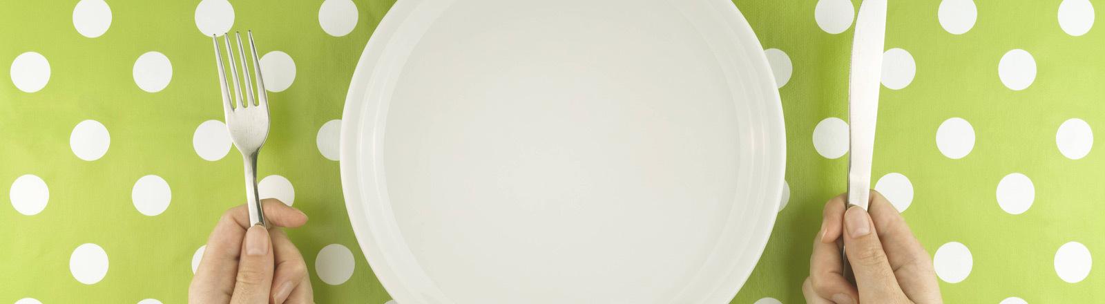 Eine Person sitzt vor einem leeren Teller.