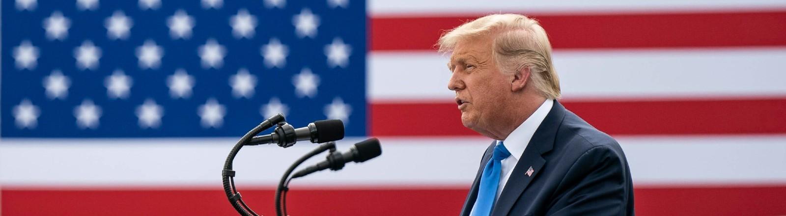 Donald Trump hält eine Rede. Im Hintergrund ist die US-Flagge zu sehen.