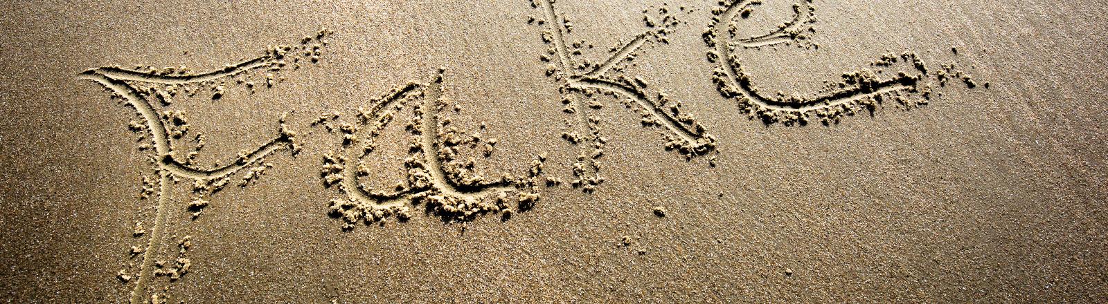 """Das Wort """"Fake"""" in den Sand geschrieben."""