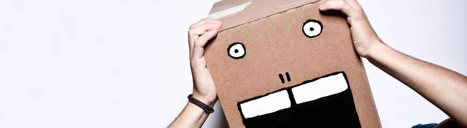 Ein Mann mit einem Karton auf dem Kopf, auf den ein schreiendes Gesicht gemalt wurde.