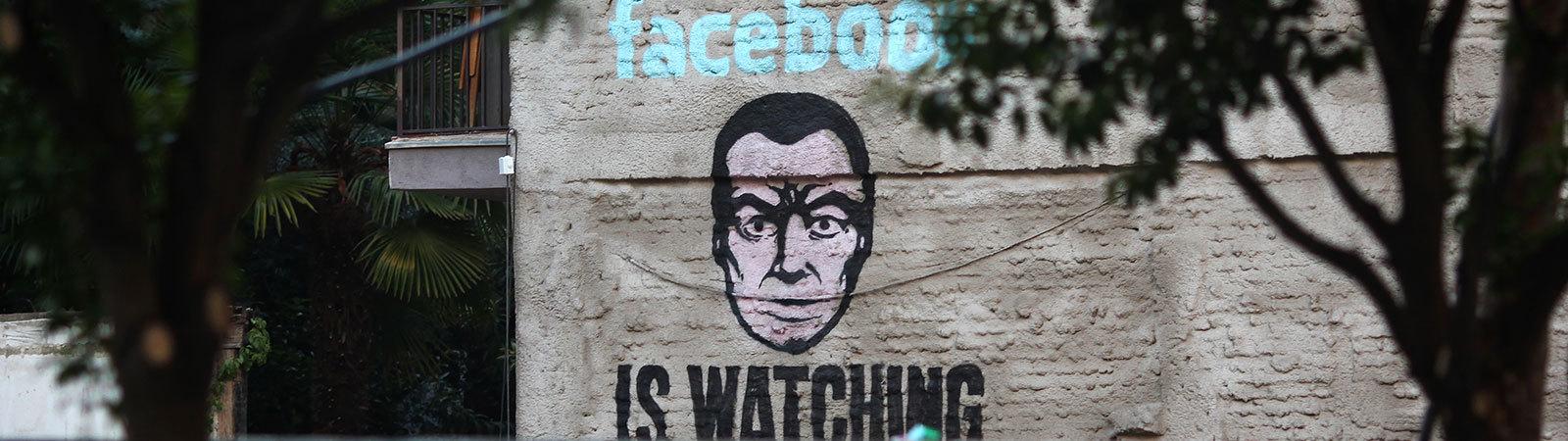 """Ein Graffiti auf dem steht: """"Facebook is watching"""""""