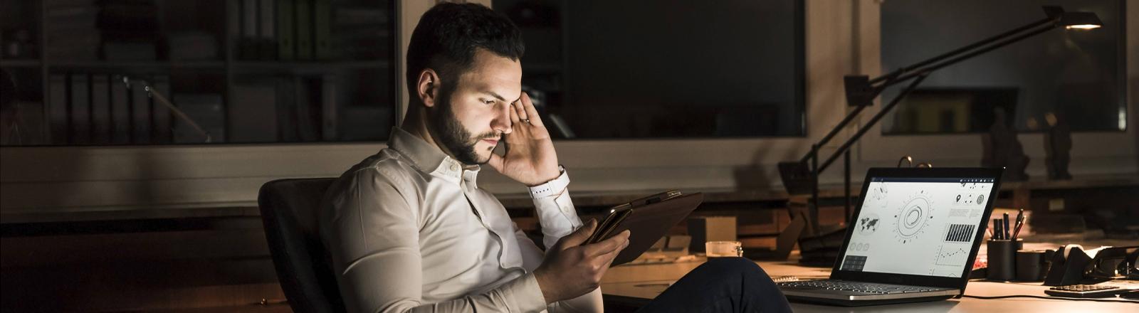 Mann sitzt mit Tablet am Schreibtisch - vor ihm auf dem Tisch der Laptop.