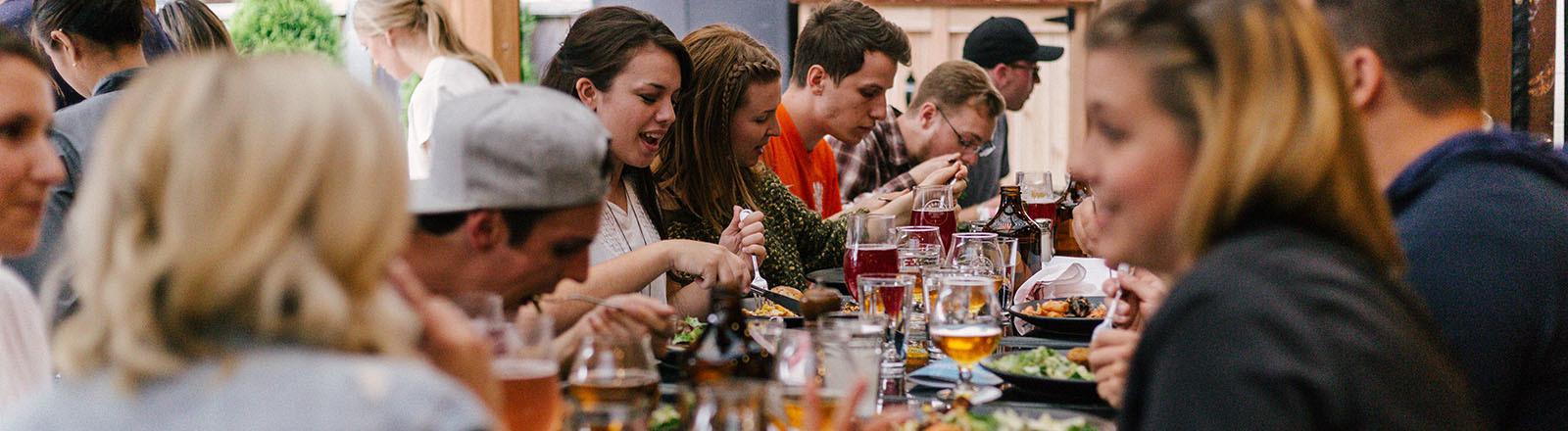 Menschen essen bei Tisch.
