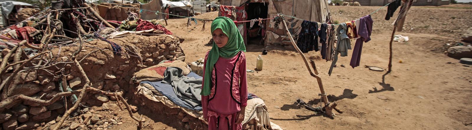 Ein Mädchen steht vor einer Hütte im Jemen.