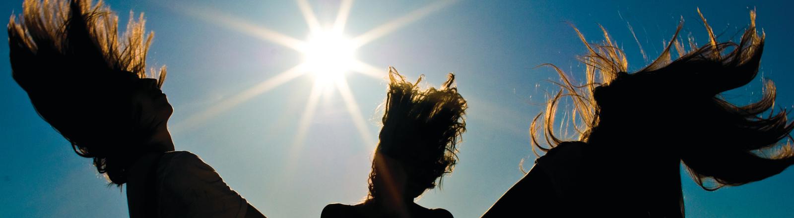 Drei Frauen mit offenen Haaren im Sonnenlicht