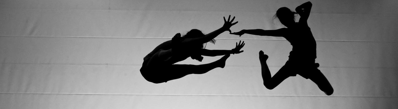 Zwei Menschen springen hinter einer Leinwand in die Luft.