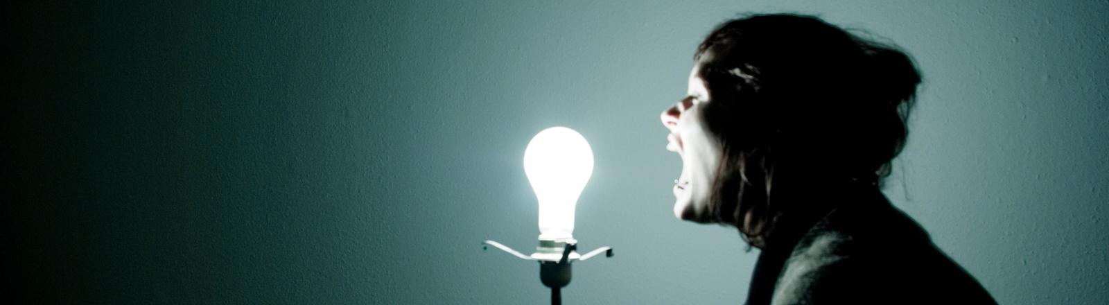 Frau schreit Glühbirne an