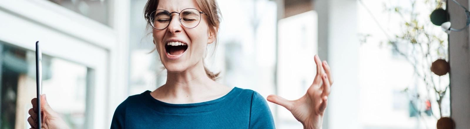 Eine Frau hält ein Tablet in der Hand und schreit.