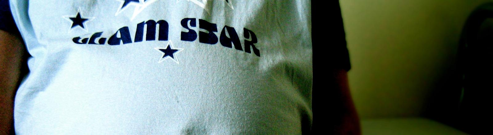 """Eine schwangere Frau trägt ein T-Shirt mit der Aufschrift """"Glam Star"""""""