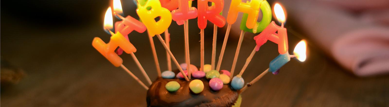 Ein Geburtstagstörtchen mit brennenden Kerzen