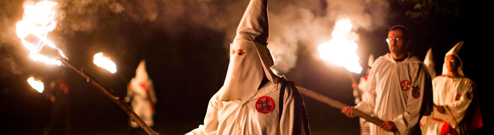 Mitglieder des Ku-Klux-Klans mit brennender Fackel