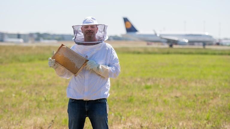 Umweltigenieur und Hobbyimker Ingo Fehr vom Flughafen Hamburg hält eine Honigwabe in der Hand vor der Landbahn.