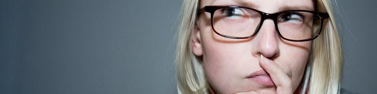 Nachdenkliche Frau mit Brille.