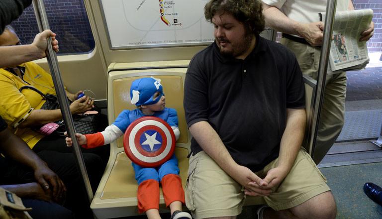 Ein Mann und ein Junge in einem Captain-America-Kostüm in einer U-Bahn.