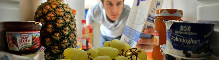 Ein Mann schaut in seinen Kühlschrank, vollgestopft mit Joghurt, Früchten, Milch, Marmeladen. Bild: dpa