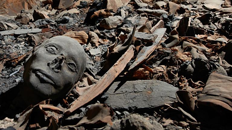 Mumifizierte Überreste zwischen Sargfragmenten, Stoffresten und Scherben.