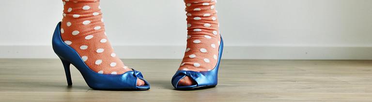 Zwei Füße in blauen Pumps mit orangenen Socken mit weißen Punkten darauf.