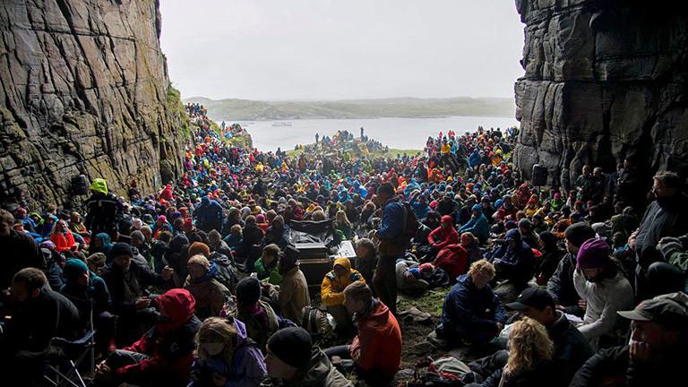 In einer großen Höhle sitzen viele Menschen mit Regenkleidung bekleidet mit Blick auf das Wasser.